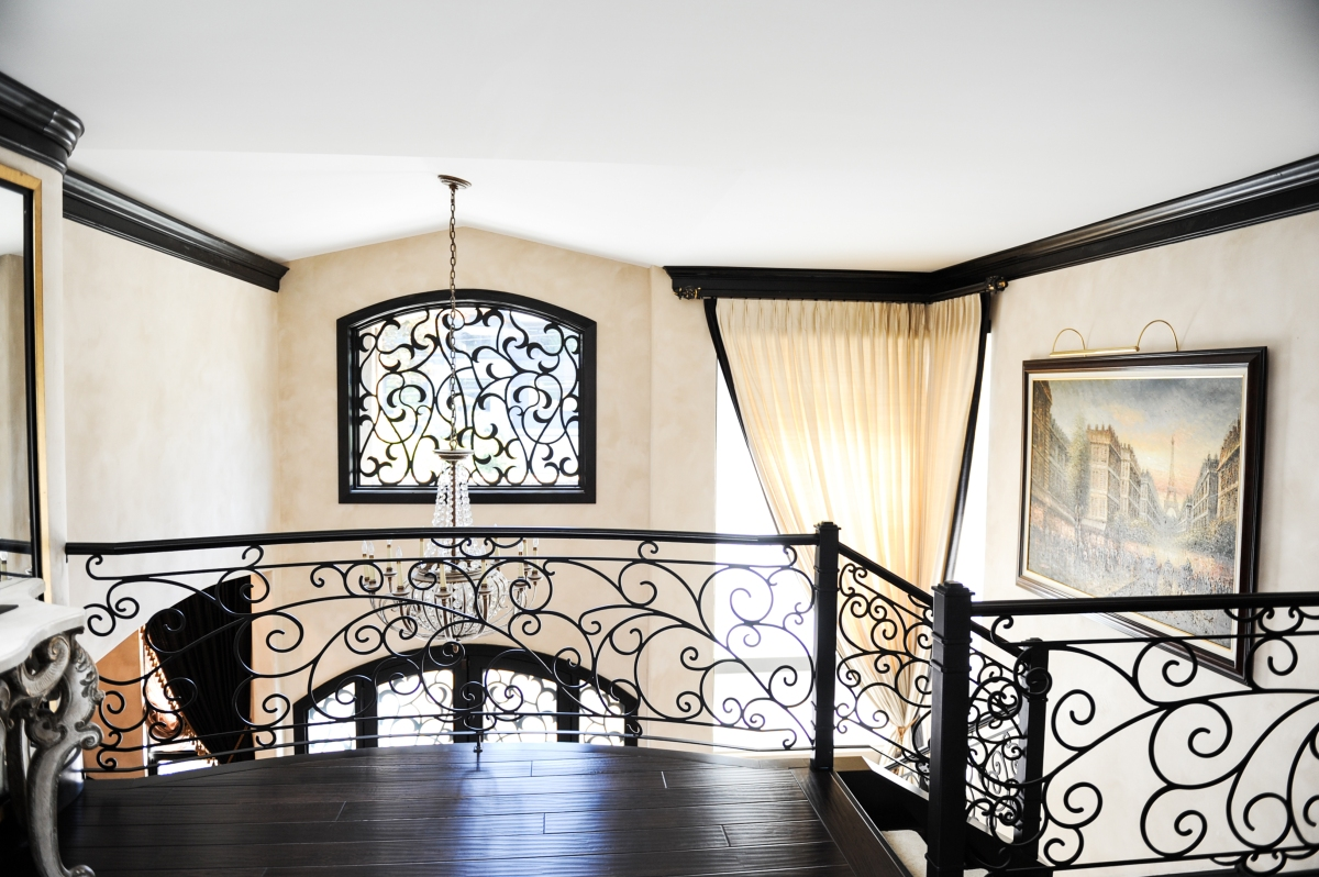 Custom wrought iron stair railing, hardwood floors, Italian plaster walls