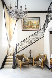 "Custom wrought iron stairs, reupholstered antique chairs, leopard print, pugs, 24"" x 24"" floor tile, Italian plaster walls"