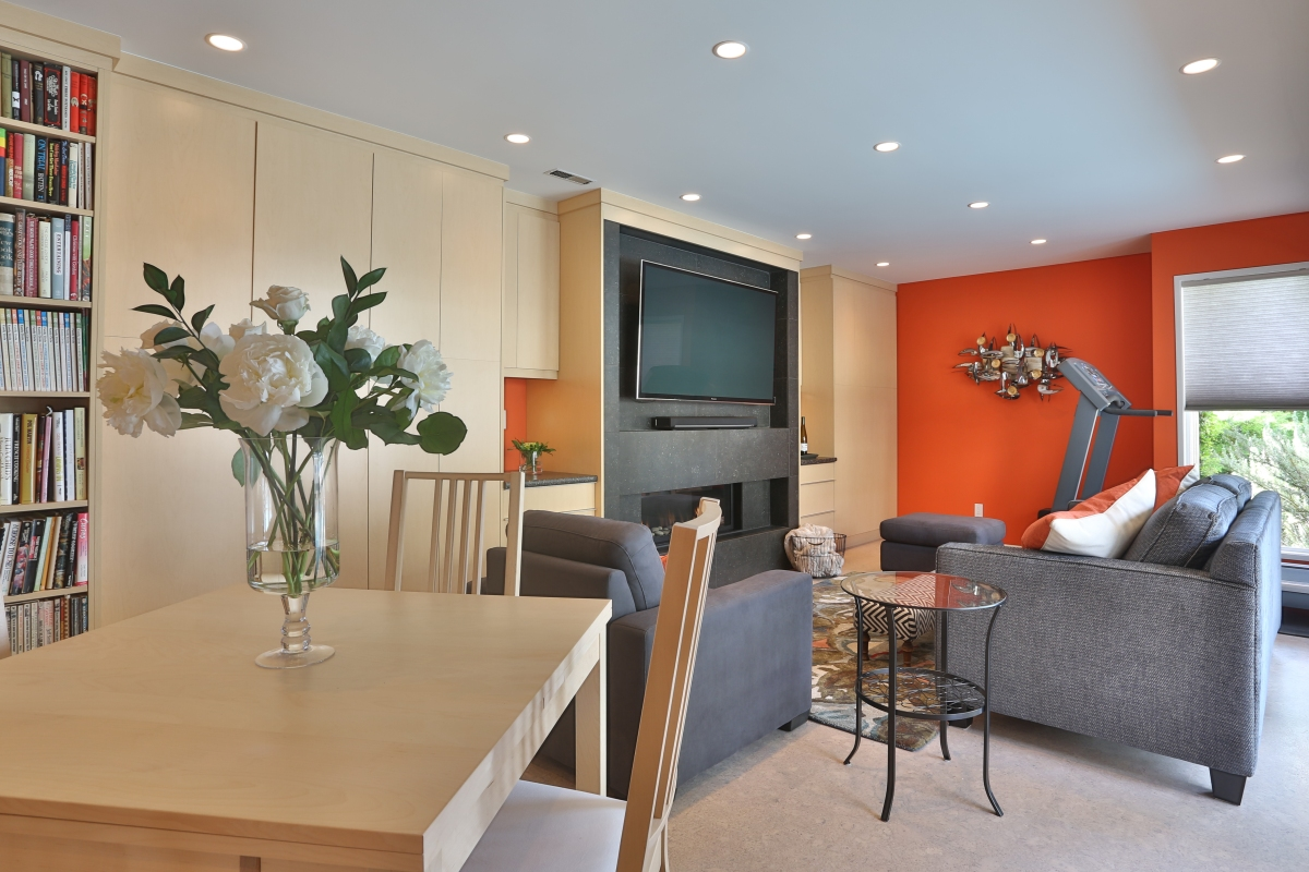 Custom built ins, fireplace, orange, bold colours, family room, flat screen tv, area rug, cork flooring