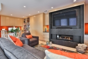 Custom built ins, fireplace, orange, bold colours, library, home office, family room, flat screen tv, area rug, cork flooring